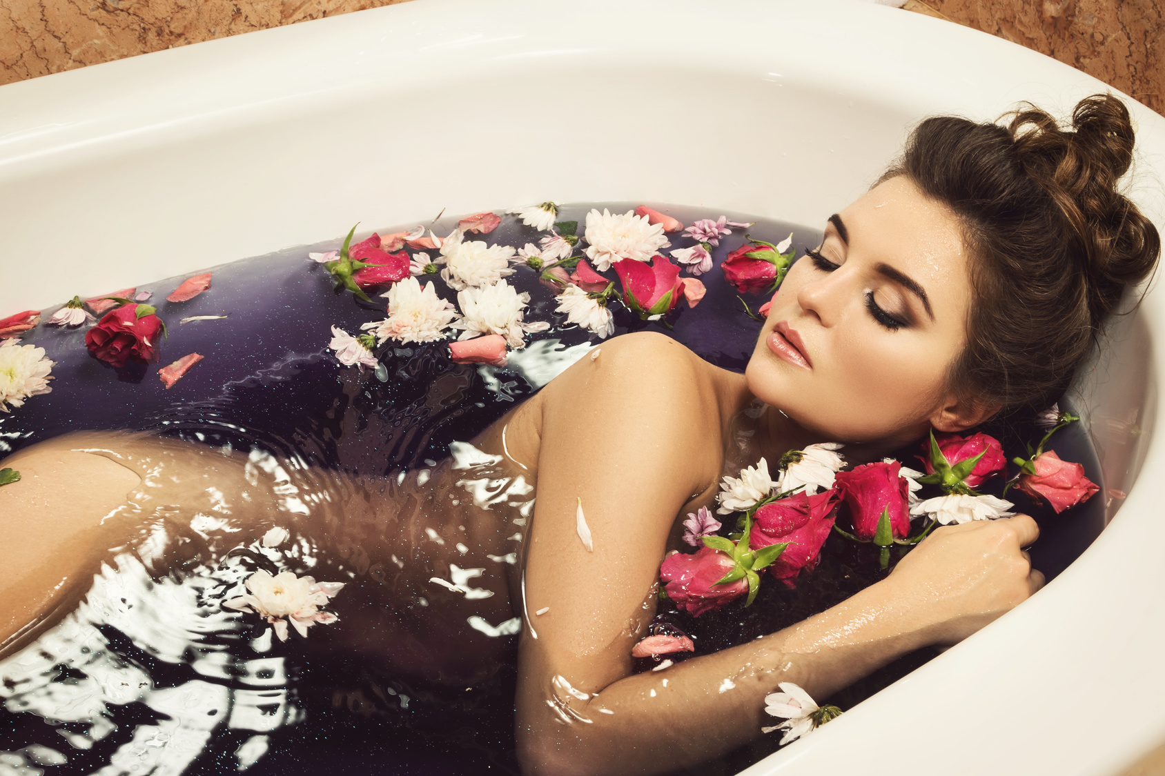 Beautiful woman in the bath with flowers. Rejuvenation and relaxation concept.